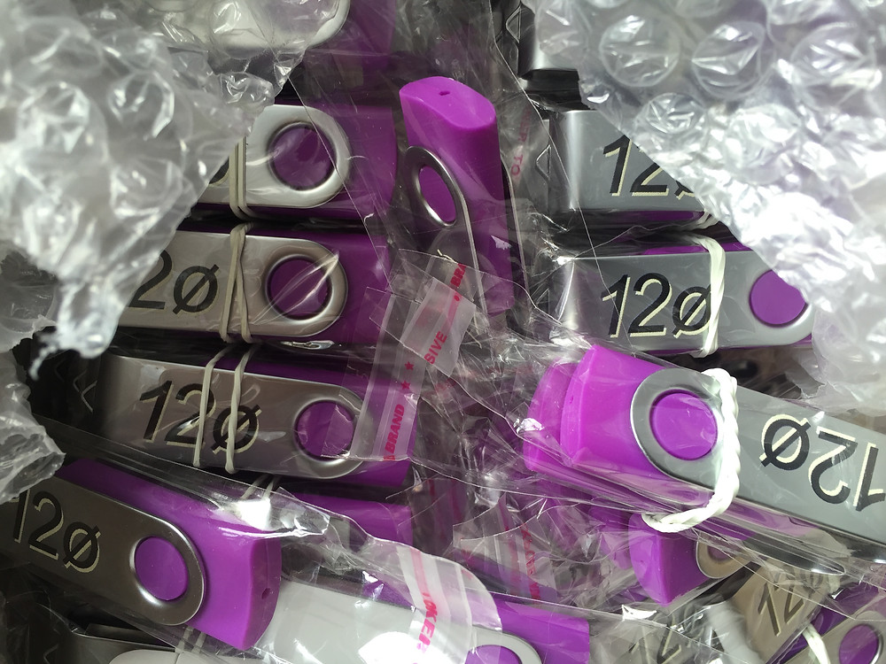 a close up of purpla and silver usb sticks each with the 12o logo on them