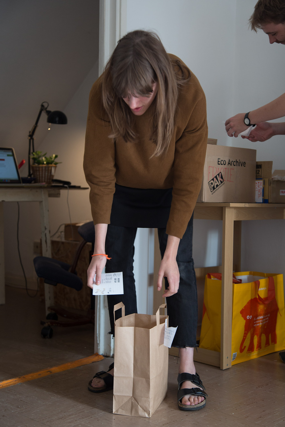 someone with long brown hair and fringe wearing a brown jumper and sandals is crouching down to brown paper bag, behnad them is a desk with a laptop and a lamp and a person checking a piece of paper in a cardboard box