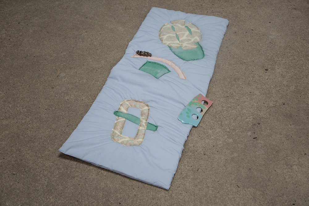 on the floor is a pale blue quilt with various abstract shapes stictched on to in pale creams and pinks and greens ,  on top of the quilt are two ceramic pieces one is a flat rectangle in blue and pink with three circles in a line cut out of it and the left is a bronze coloured piece in the negative shape of a hand grip.