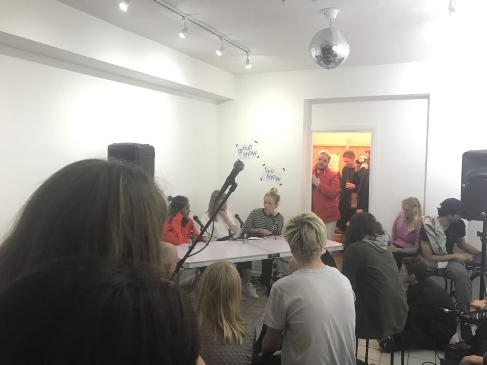Zarina, Caitlin and Lou seated behind a table with microphones, photo taken from behind other seated audience members.