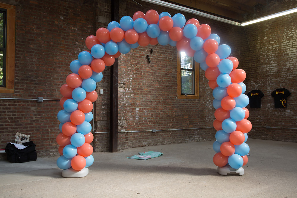 an photograph inside a raw brick building with high ceilings and a window in the background, the floor is raw concrete. The centre of the image is a very largew ablloon arch made of a twist pattern of alternating blue and red balloons, the column of the arch is about 6 balloons wide.,