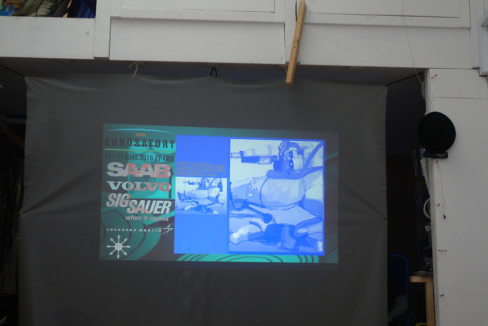 A photo graphy of a projection of the nawki show real, with the still of the work showing an inverted colour graphic, the image shows car manufacturers names and green background and a blue image infront. the works is projected on the a screen made of grey fabric , pinned up to a white studio wall .