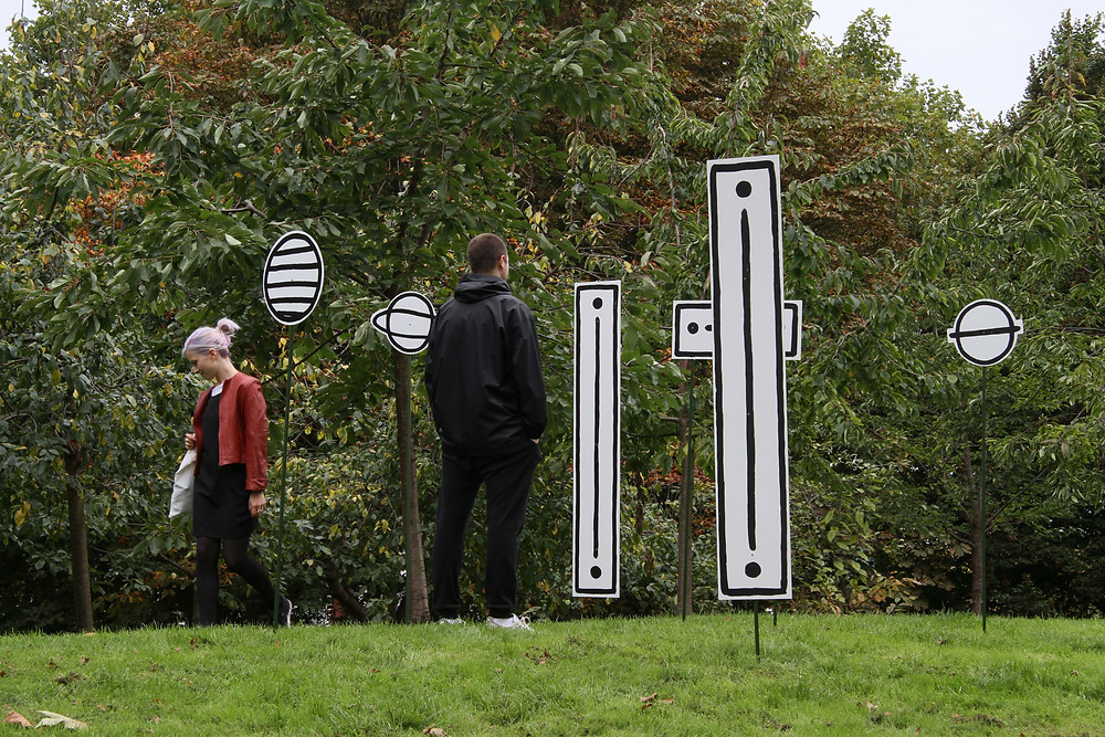 a photography of outside in a park with green grass and a wall of various types of trees in the background and grey sky. In the foreground are two people one with lilac tied back hair and a red jacket facing towards to camera, the other has short brown hair and wearing all black, and facing away from the camera, they are both looking at the artworks, that are a cluster of 6 various poles withoutlines of rectangular and circular shapes drawing on white board with black outline, they are stuck into the ground so that they stand upright.