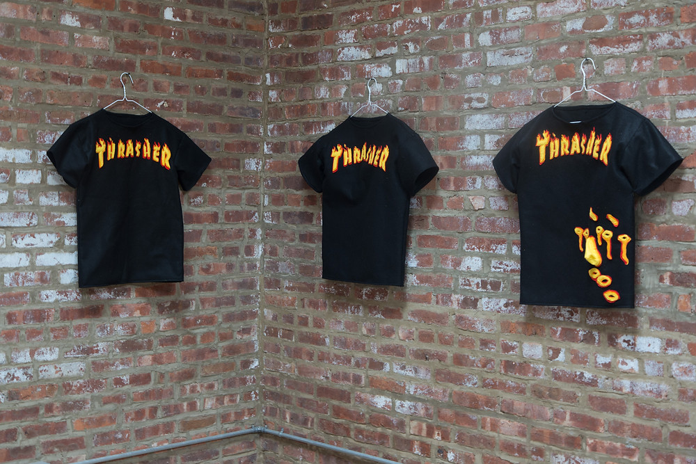 a photo graph with a brick wall with three black t shirts hung on the wall with coat hangers, each t shirt has the words thrasher on the in white font with a red outline. the font is in flames.