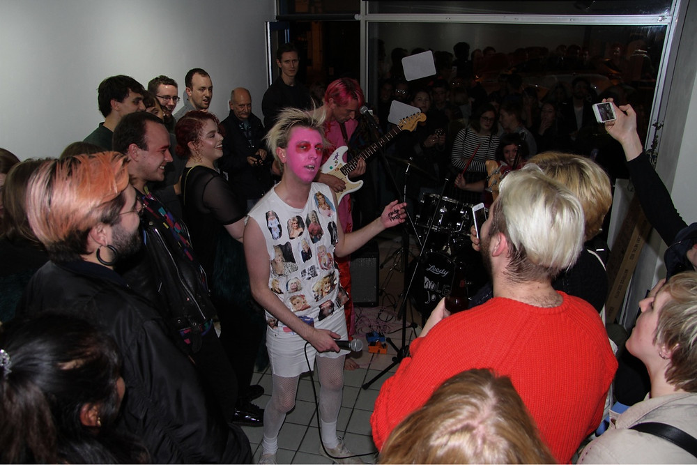 Aidan Strudwick performing with Molejoy, in the middle of a crowd inside a small shop space.