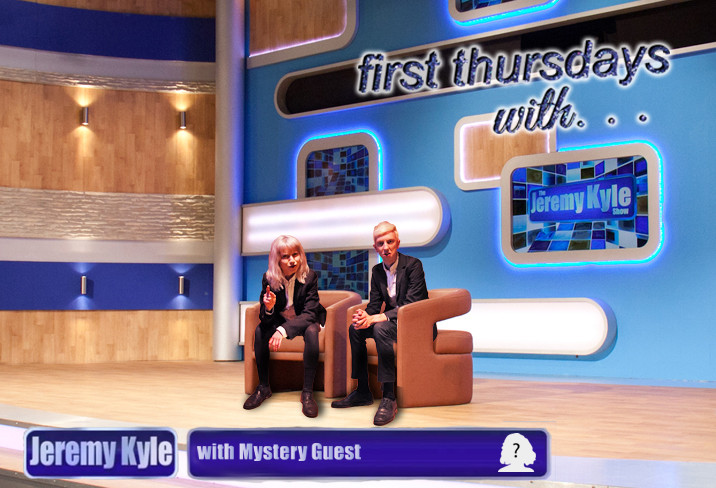 a image of the jeremy kyle studio set, the set has wood panneling and various sqaured lights and blue walls with a screen reading 'Jeremy Kyle' in front is a laminate floor stage and two brown modernist style chairs, on the chairs are the two performers 'Kat' who has white blonde long hair with a fringe, she is wearing a suit and white shirt and leaning forward on to her knees and point and the camera. the second chair is 'Aidan' who wears the same outfit as 'Kat' and is sat with hands clasped. he also has white blonde hair. at the bottom of the image reads a screen text ' Jeremy Kyle , with mystery guest'. At the top right hand corner reads 'First thursday with...' in purple writing.