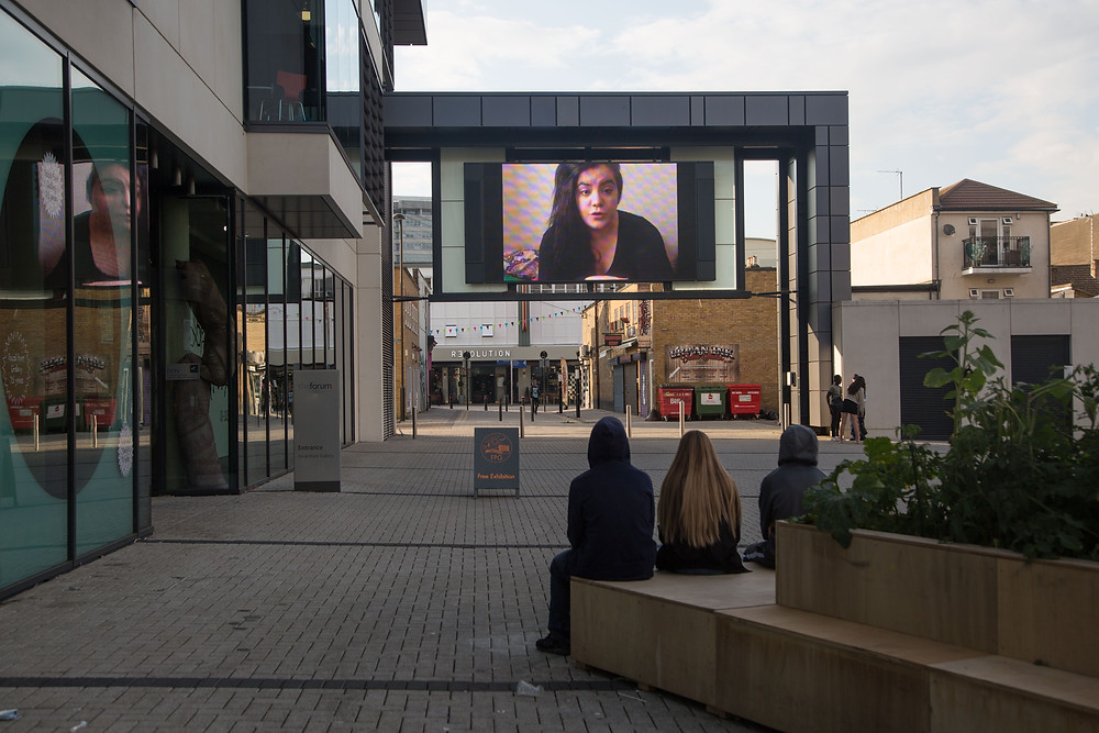 a photograph outside focal point gallery of their big screen in the square outside, the screen is suspended by a walk way. around the screen and the buiolding next to it are grey panels and large glass windows. Behind the screen you can see a road that leads to shops and people walking. On the screen shows a still of a work by an artist in nawki, the still shows a woman with long black hair talking to the camera. .