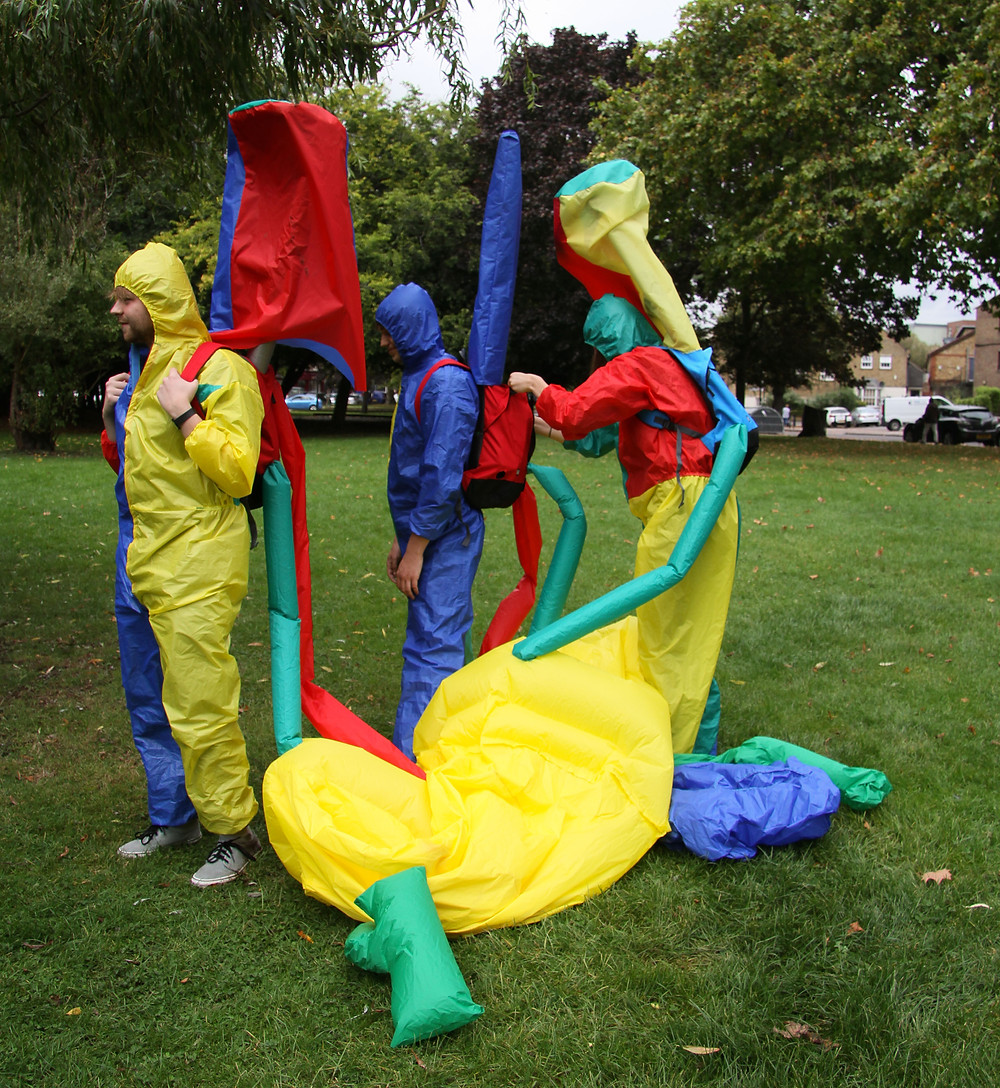 a photography of outside in a park with green grass and a wall of various types of trees in the background. In the foreground are three people, each wearing a brightly colour suit with a hood , they are all greens yellows, reds and blues, they are all wearing backpacks with tubes of the same material coming out of the bags, this then attached the a large inflatable in the same material on the ground in front of them. the three people are all faceing the left, the first left person is holding their bag arm straps the second is being helped by the third with the something in their bag.