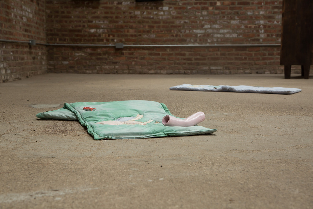 a ground level persepctive photography of a work mad eof pale green quilt that is folded on the ground, on top is a pink ceramic tube , in the bacground you can see another pale quilt laying out flat.