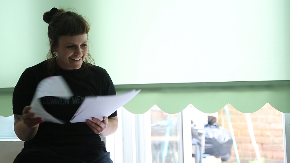the artist reading from sheets of paper in front of the green window blind. they are smiling and have dark brown hair with a fringe and tied into a bun.