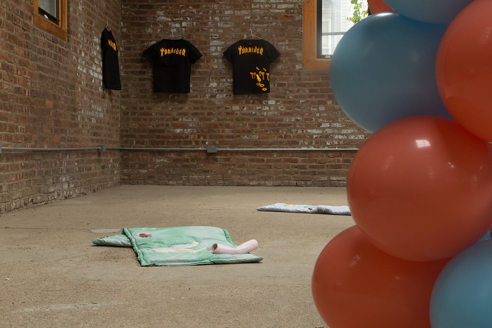 an image inside a brick walled room, the images has the red and blue balloon arch just in the right hand side of the photo in the immediate foreground, behind are the two quilts of the floor with ceramics placed on them and that far background are the three black tshirts on the wall with the words thrasher on them