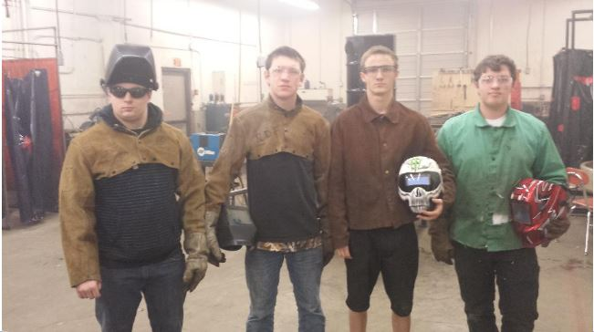 Welding students pose in shop
