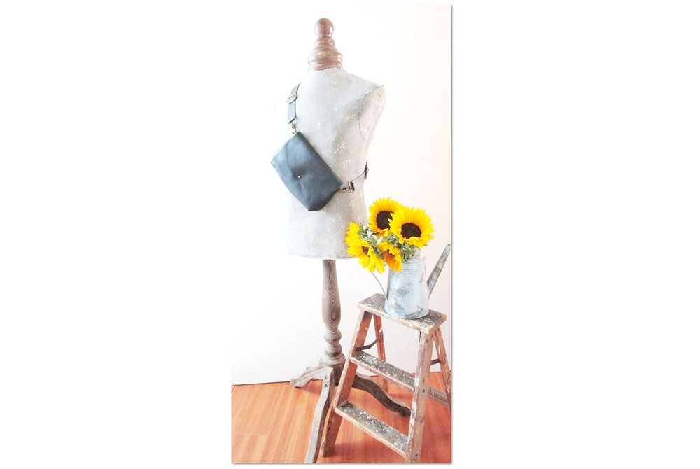 Vintage Mannequin with Pelt And Post Convertible Leather Bag Next To Sunflowers On an Aged Watering Can on a Vintage wood Stool