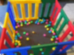 rainbow coloured plastic play pen filled with balls for hire