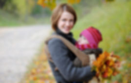 mother carrying her baby girl in a front pack while collecting autumn leaves in Arrowtown New Zealand