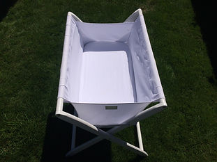 White Cariboo folding bassinet set up in Queenstown hotel for a baby on holiday