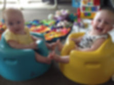 happy cute boy girl twins sitting in blue and yellow Bumbo seats in Queenstown hotel
