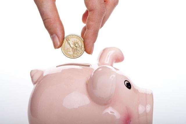A piggy bank with a hand putting some change on the inside.