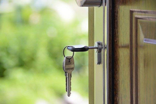 A silver set of keys in a wooden door.