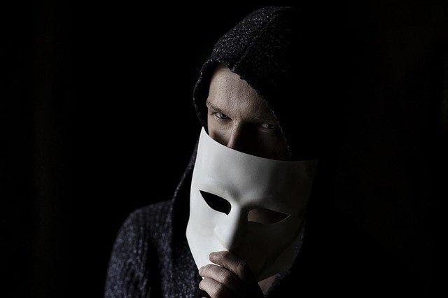 A white man with a black background. He has on a black hoodie and has a comedy/tragedy mask covering half of his face, and you can see his eyes.