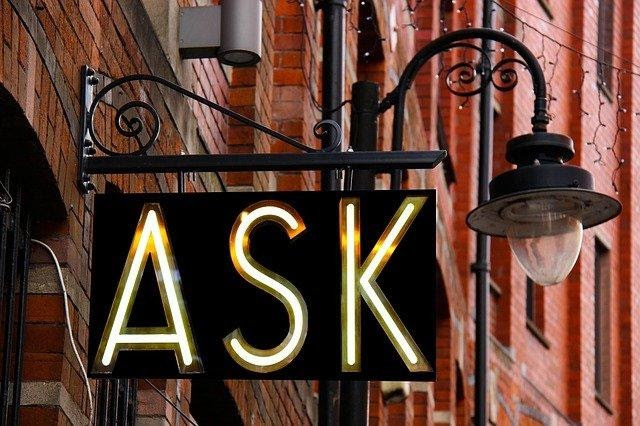 """A sign on a building with neon lights that spell """"ask"""""""