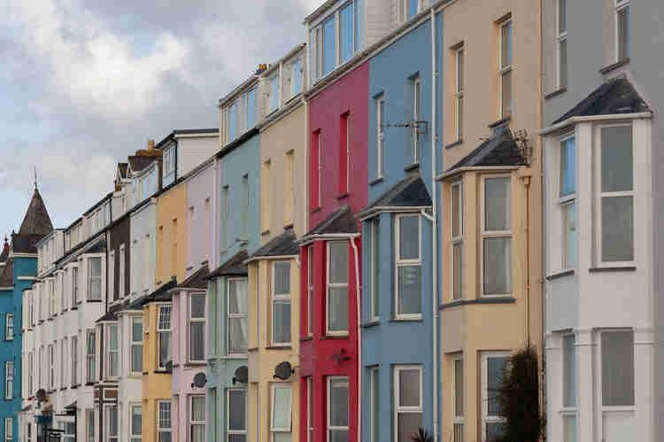 Apartments lined up on a street painted in different colors.