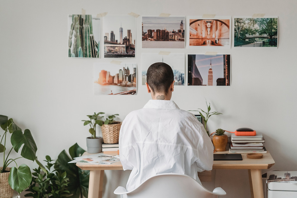 a lady with a low hair cut sitting at a desk with photos on the wall, plants to the left of her and her back to the camera.