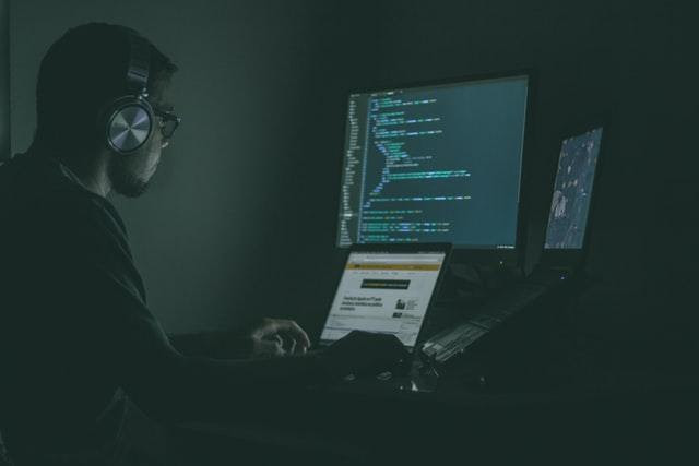 A man with earphones on a several computers, looks like he is gathering data or hacking some software.
