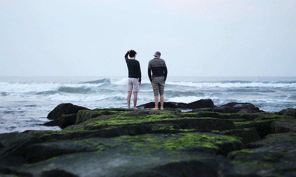 Two Men standing on a rocky outcrop, overlooking a stormy sea.  The sky is a washed out grey and the sea is also reflecting the greyness.  The rocky outcrop is covered in moss