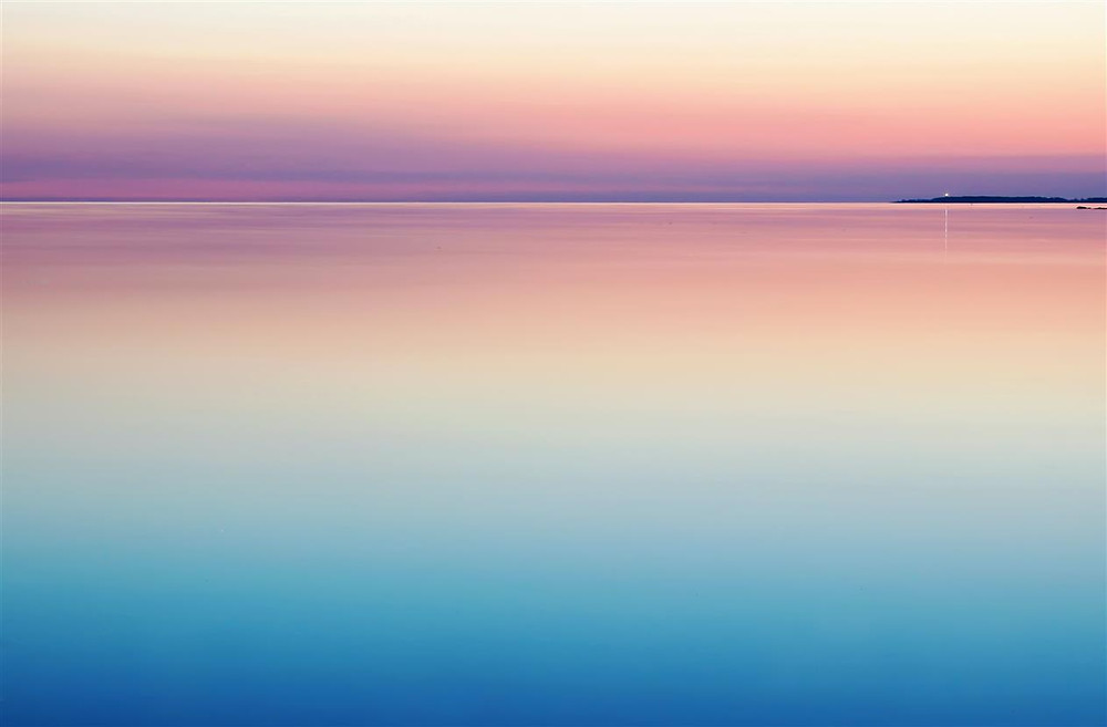 A calm sea in pastel tones, The sea in the foreground is purple, then fading through to blue, then red into the horizon, when turns to the sky in shades of pink and orange