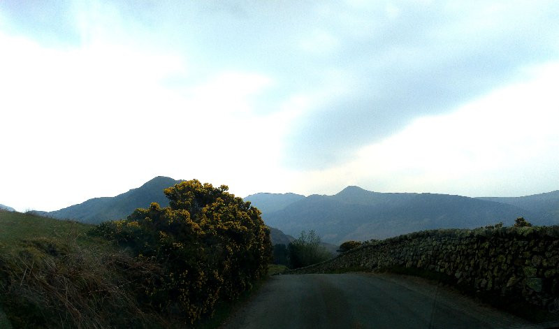 A Road rising upwards along which the viewer is travelling. In the distance are the fells of the Lake District