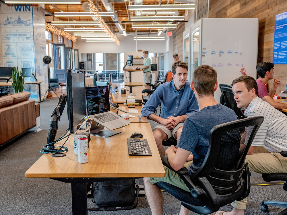 A Modern Opem Plan Loft Style Office. People are working on Computers and in the foreground a meeting is taking place at one of the open plan desks.there are three men talking to each other. Two of the men are wearign Shorts and the 3rd mais dressed in a Short Sleeve Shirt and Chinos