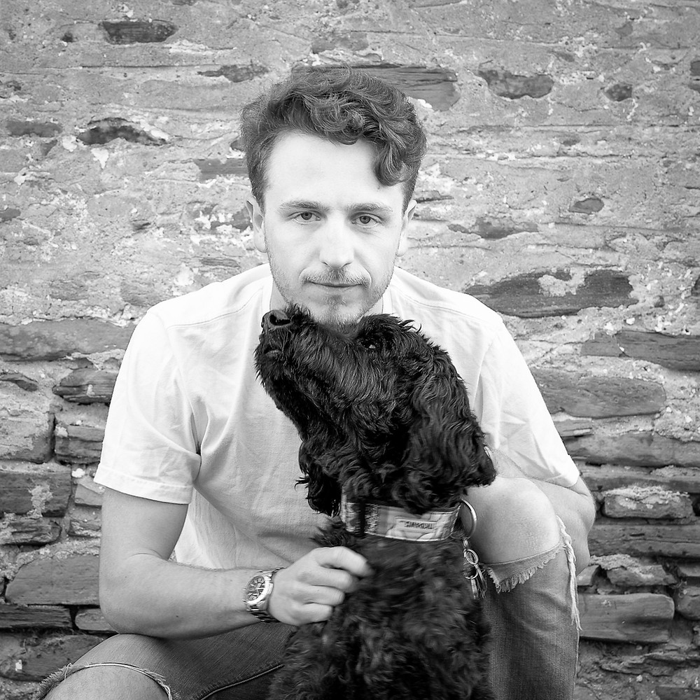 A young man looks at the camera while his black dog leans towards him for a snuggle.