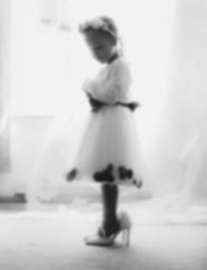 Flower girl trying on brides shoes