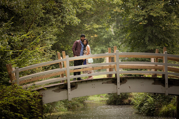 Couple standing on a bridge in a rain shower