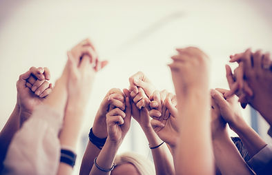 stock photograph of multiple sets of hands clasped together