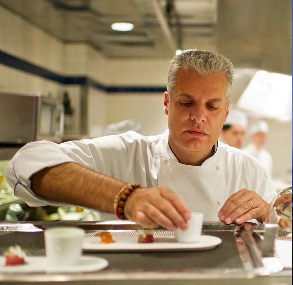 Chef Eric Ripert plating food in the kitchen