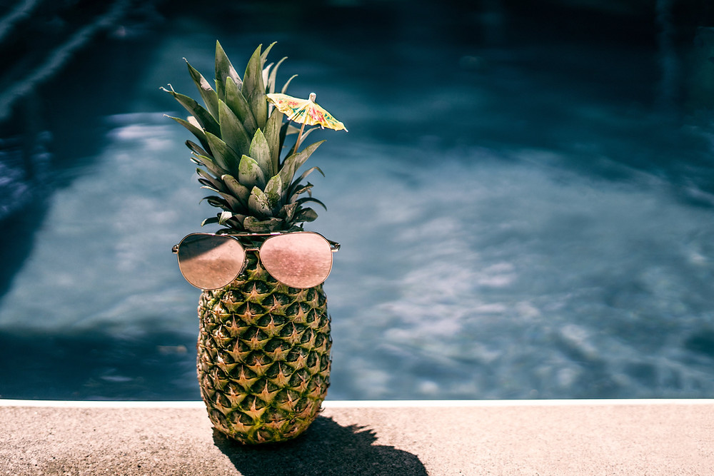 Pineapple wearing sunglasses by a pool