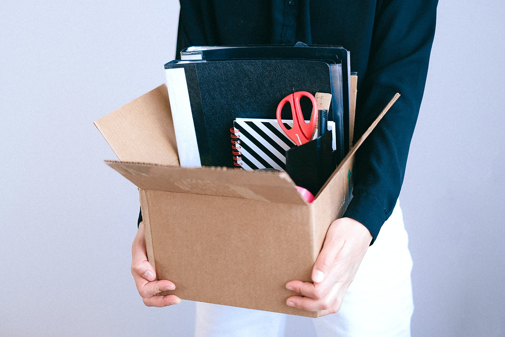 A person stands in front of a grey wall. They're holding a cardboard box filled with items from an office desk: folders, a notebook and a stationery pot.