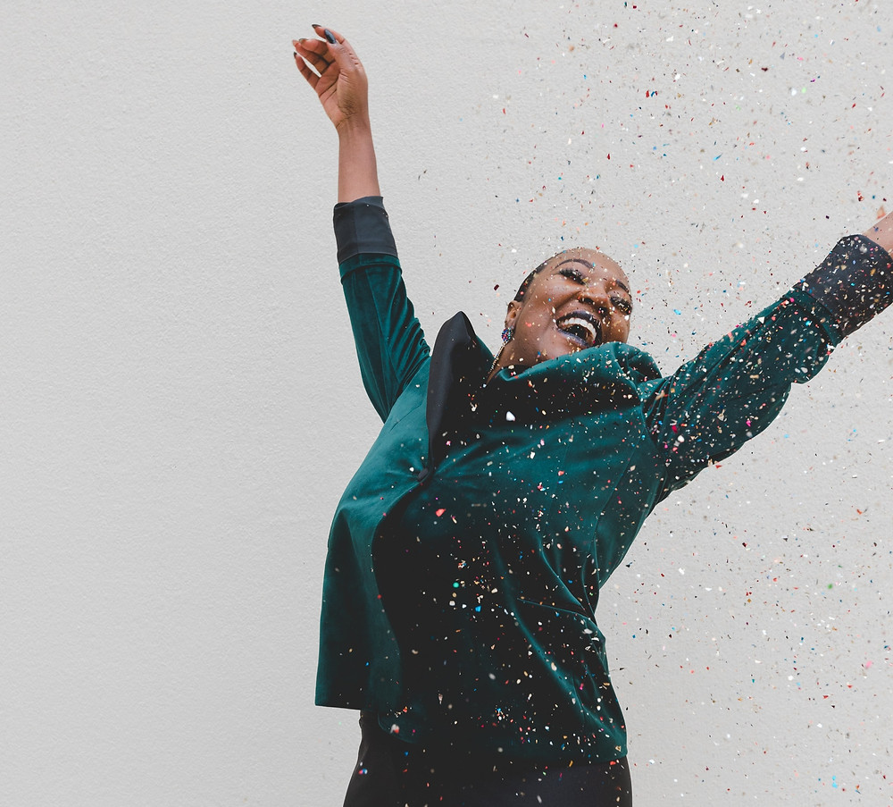 A woman wearing a dark green velvet blazer throws her arms in the air. She smiles as multicoloured confetti rains down on her.