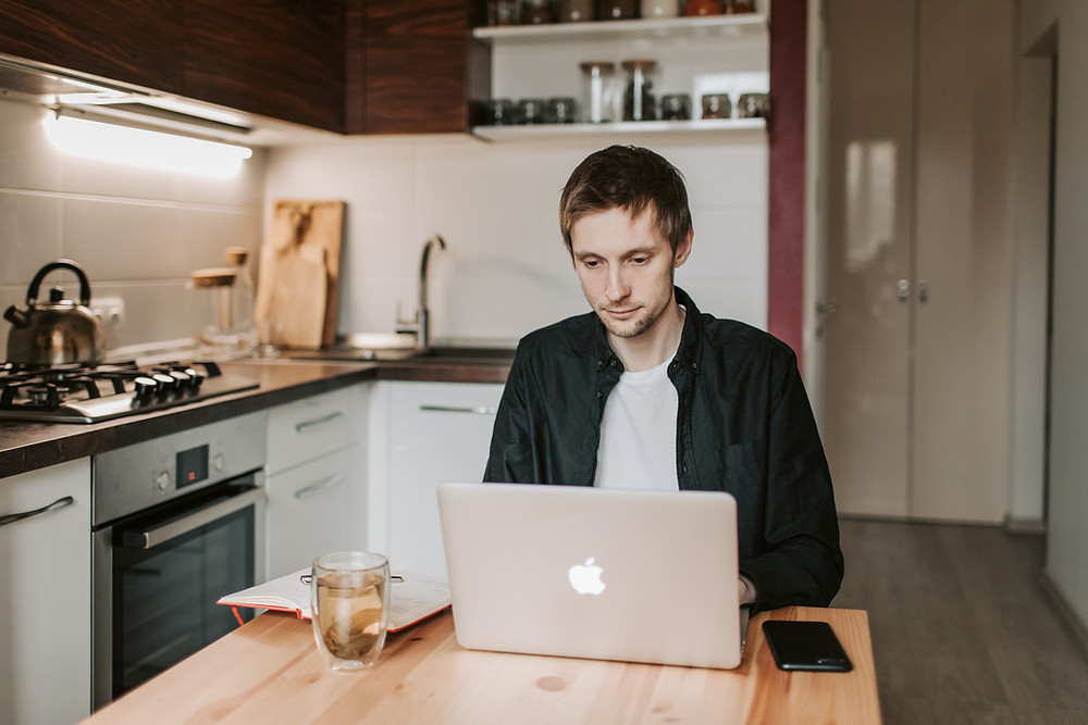 A man sits at a dining table in a small modern kitchen. He appears to be working from home; With a notebook and hot drink to his side, concentrating on an open laptop.