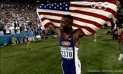 Micheal Johnson holding a USA flag during his win in the olympics