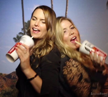 Two girls singing while holding a Mcdonalds coke cup