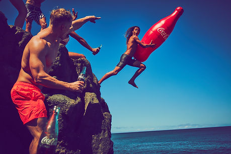 guy jumping off a cliff while holding a inflattble coca cola bottle