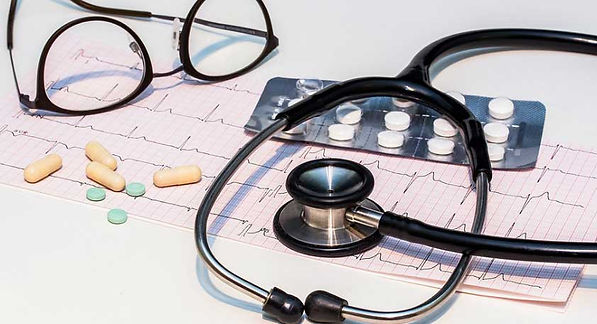 ECG chart, pills, stethoscope and doctors glasses.