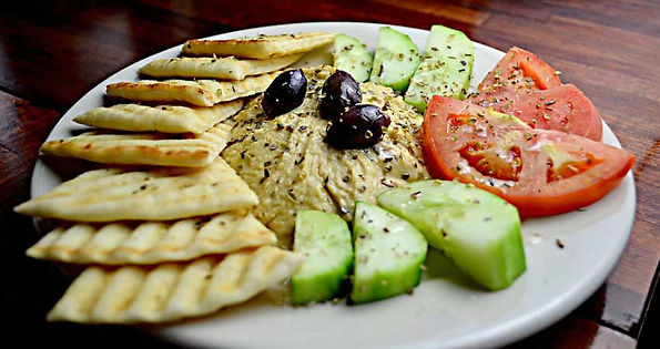 Plate with hummus and vegetable and bread.