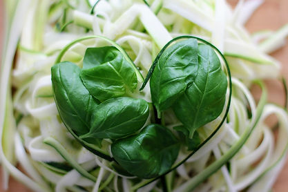Basil wrapped in zucchini in the shape of a heart.