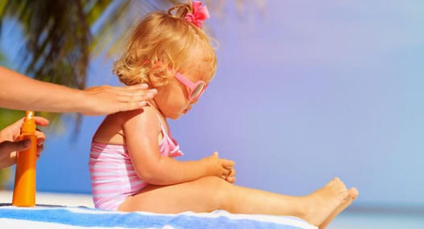Mom applying sunscreen to her little girls shoulders. Sunscreen Safety