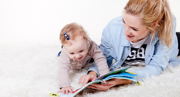 Mom and baby girl playing with a book. Getting Your Child to Read