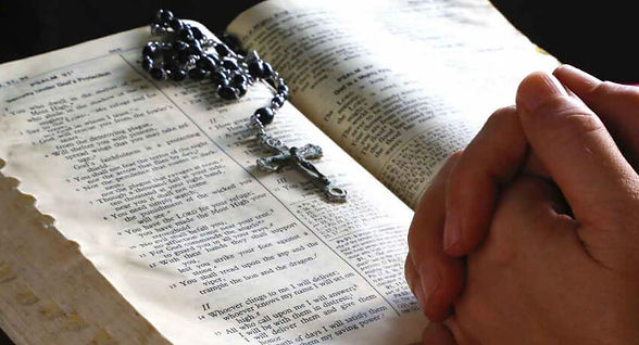 Hands folded and the Bible open. In Search of Spirit.